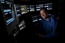 Photo of Prof. Matt Wilson sitting in front of multiple computer displays.
