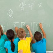 Photo of several children writing on a chalk board