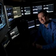 Photo of Prof. Matt Wilson sitting in front of multiple computer displays.