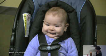 infant in seat watching video of woman picking up ball