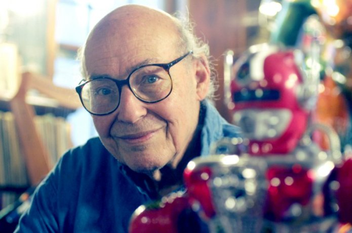 Photo of Marvin Minsky with a toy robot in the foreground. Photo Credit Boston Globe
