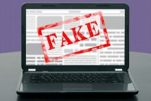 "Image of a laptop displaying an article that has been stamped ""Fake"""