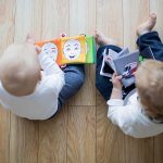 two infants sitting reading books