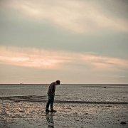 lonley man wlaking on a beach